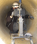 Staff inside a pipe working with tool