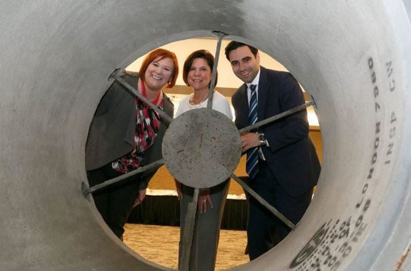 Staff members behind an open pipe